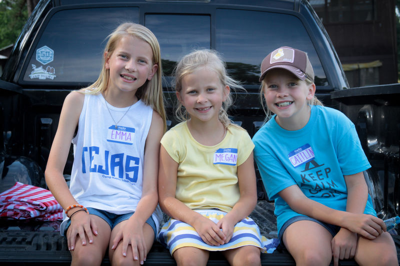 The Doyle girls perched on the bed of the pickup truck at Cookout