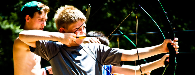 Archery | Learn to arch like Robin Hood on our renovated, 14 target archery course.  Tanner (6 yrs at camp, 2nd generation camper) pulls back looking for a bullseye.