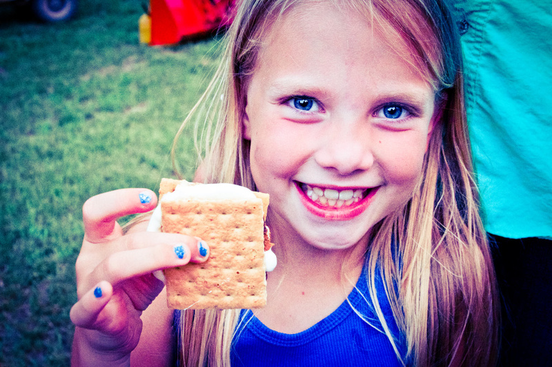 Caitlin (5 yrs at camp, 2nd generation camper) gets ready to take a big bite of her s'mores after Fishing.
