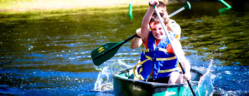 Canoes - Tucker (7 yrs at camp, 2nd generation camper) paddles hard trying to win individual comp at canoes.