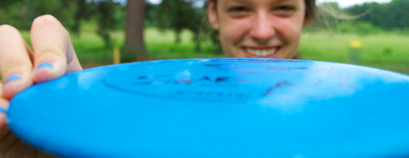 Frisbee Golf | You may find a love for frisbee golf once you play the scenic Huawni Pines course, established in 2003. Claire (10 yrs at camp) smiles during an after supper round.